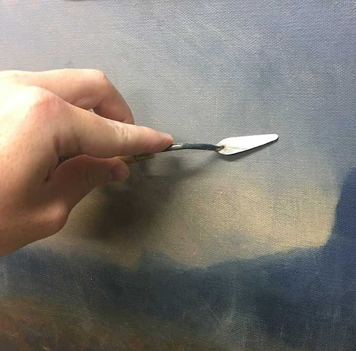 Using the palette knife to scrape away paint